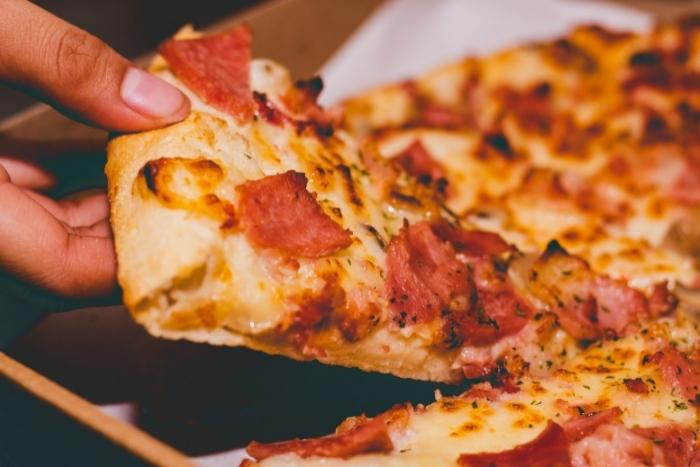person-taking-pizza-slice-for-nyc-food-tours