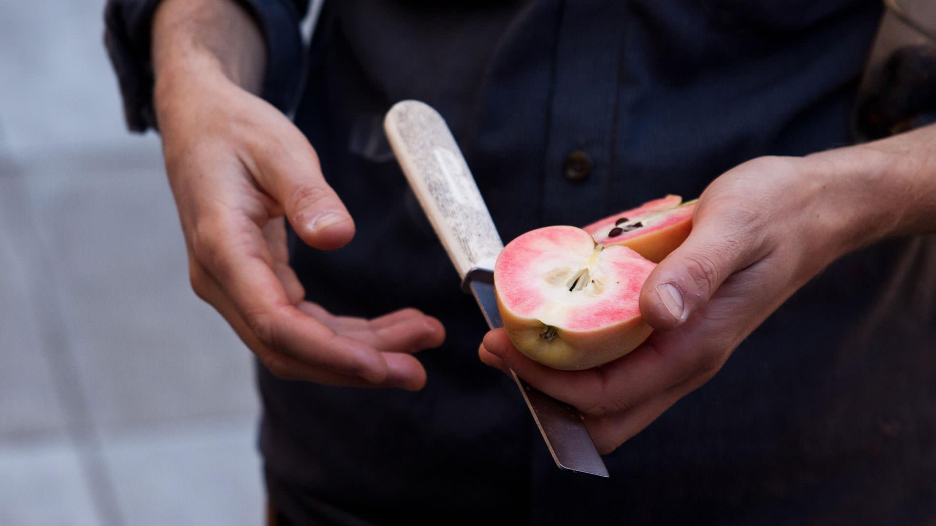 Man cutting peach with knife
