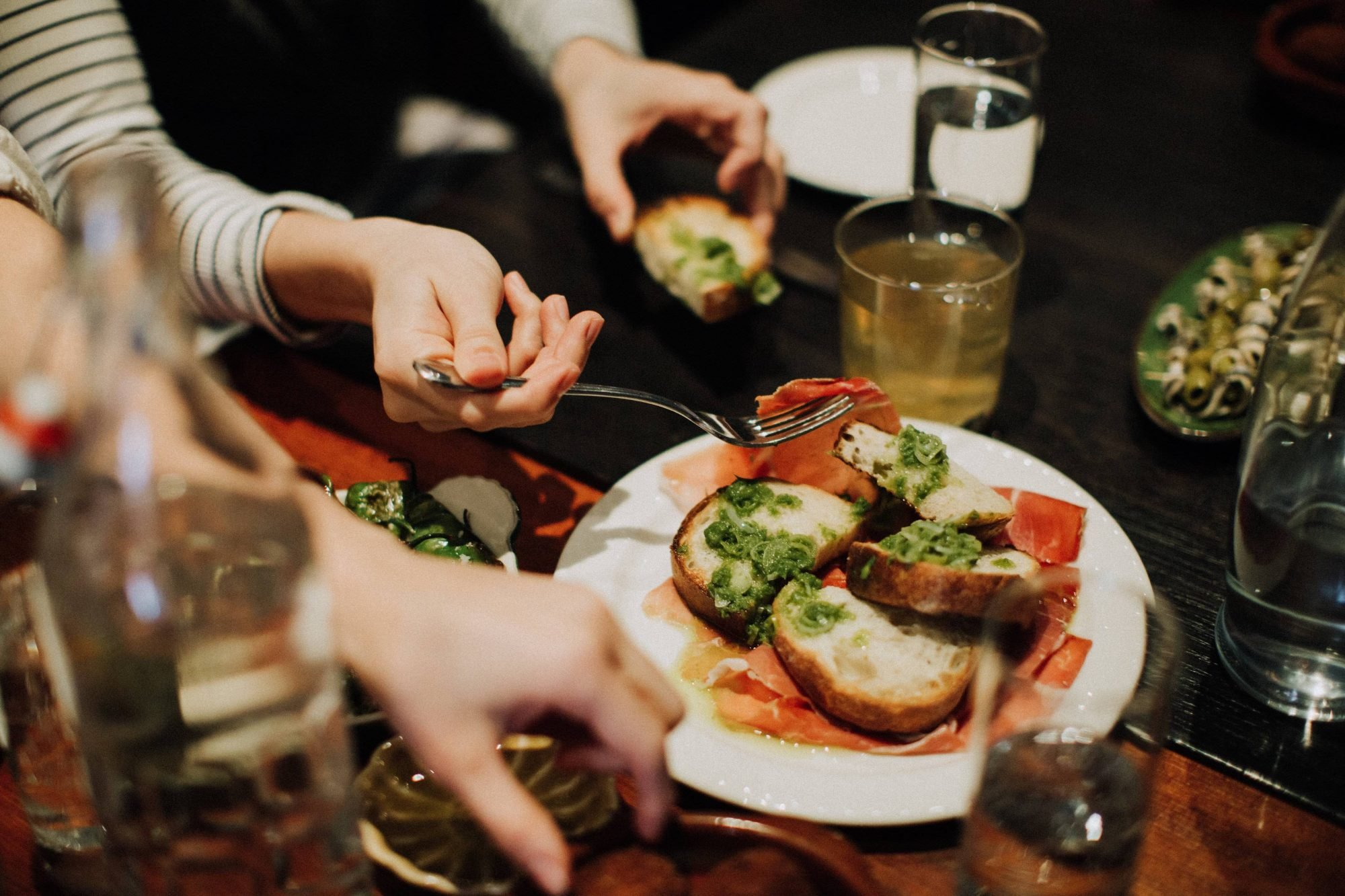 hands reaching for spanish tapas in dimly lit restaurant hosting bachelorette party food tours