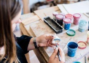 woman painting clay bowl 50th birthday party ideas quarantine
