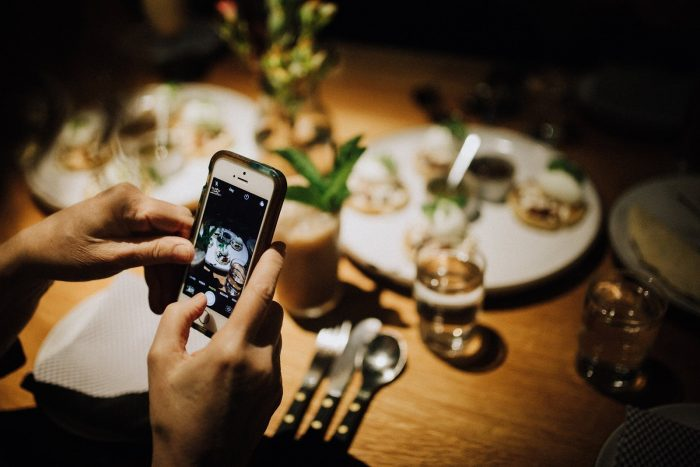 person taking picture of food to engage and thank clients virtually