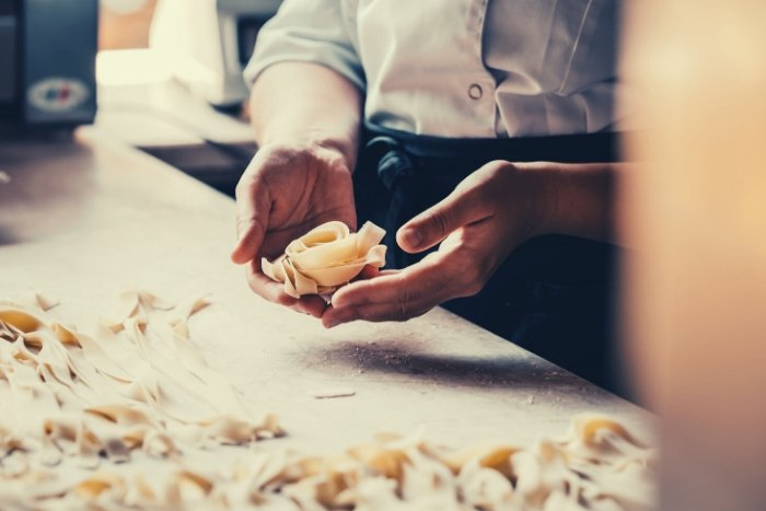 woman making pasta for virtual thank you ideas for clients