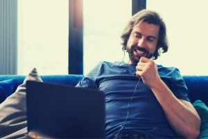 man with laptop laughing how to host a virtual happy hour