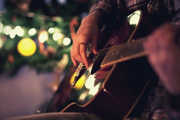 playing christmas music in front of tree