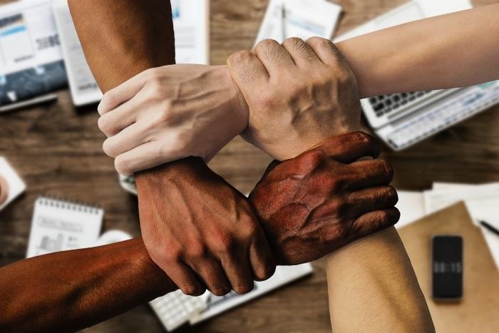hands-holding-wrists-to-indicate-team-building-activity