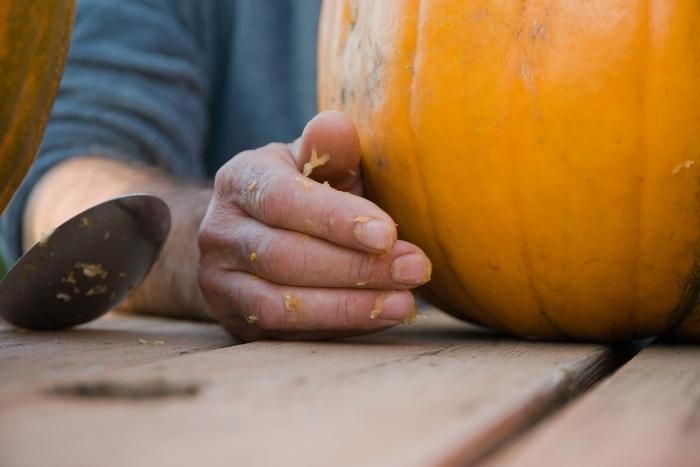 man-carving-pumpkin-during-virtual-halloween-party