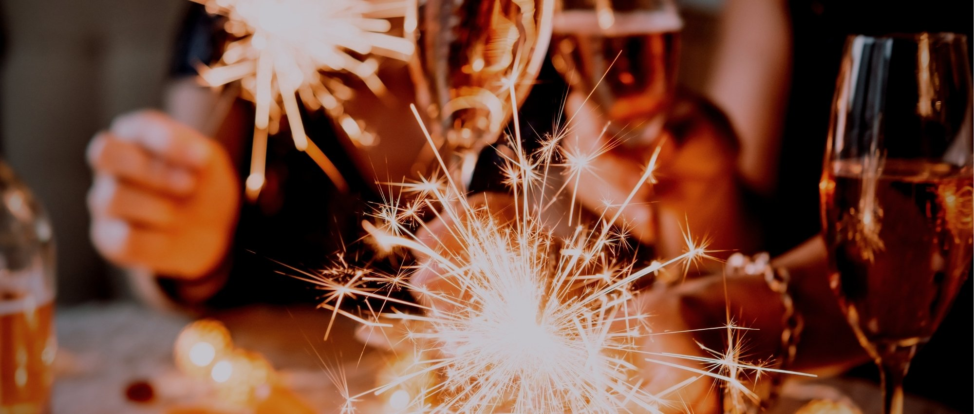 people drinking champagne with sparklers