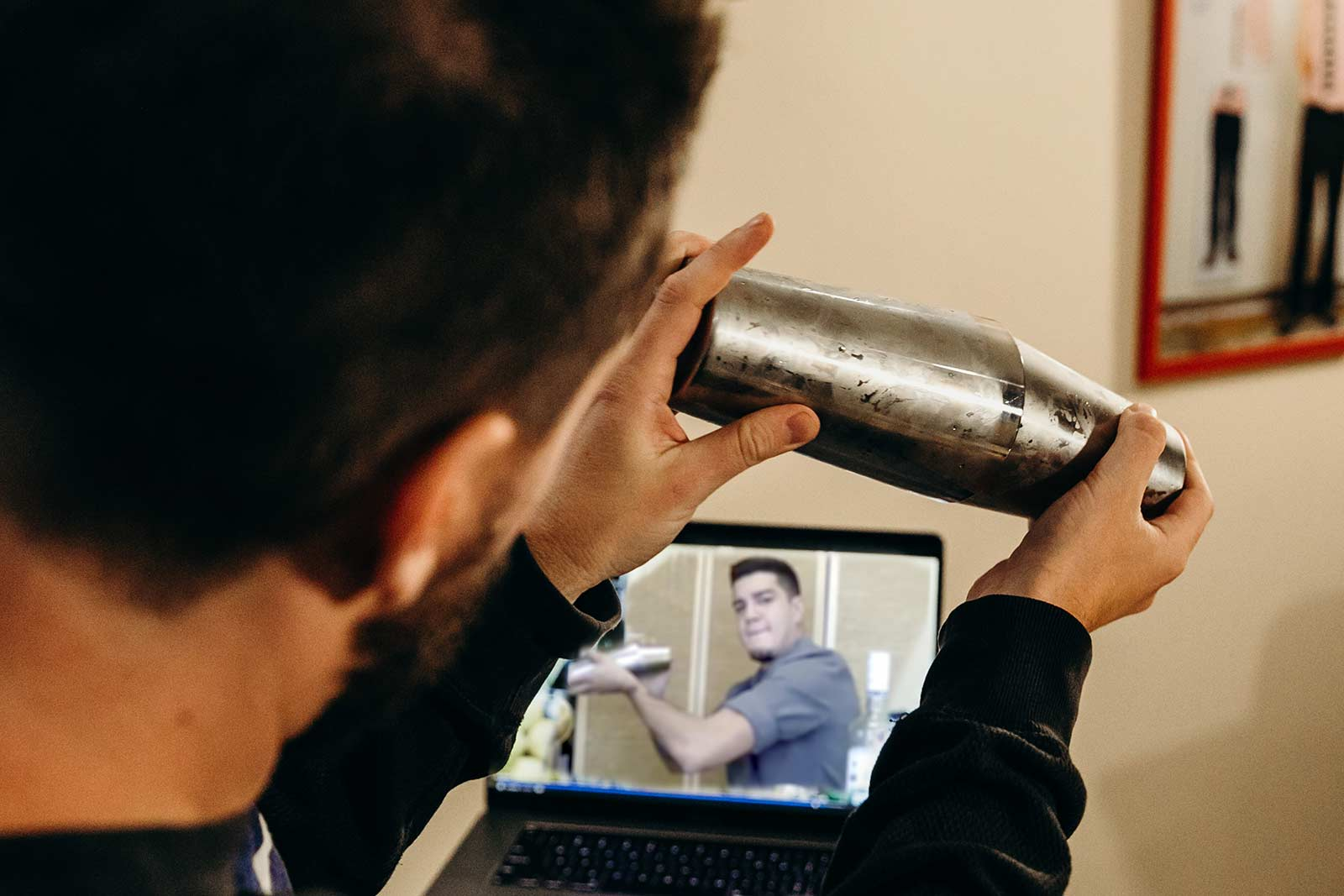 man shaking cocktail during virtual events happy hour