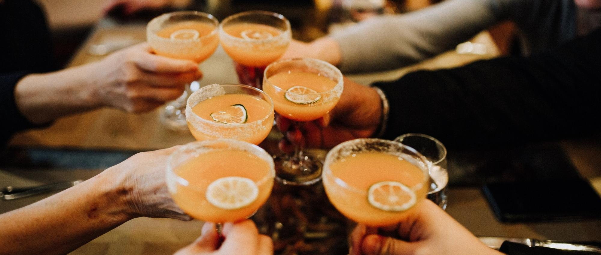 team building group cheersing cocktails during food tour